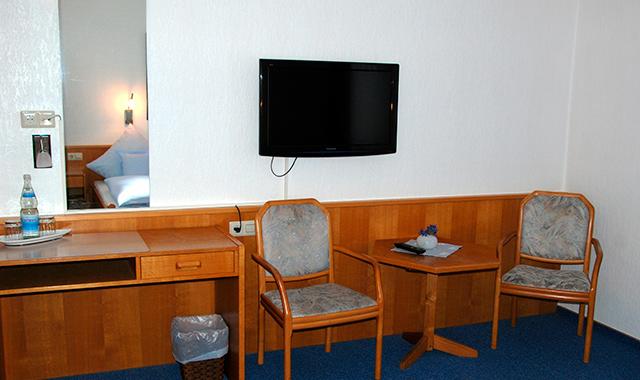 Hotelzimmer mit Schreibtisch, Sitzecke und TV